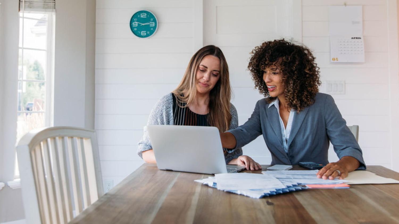Zwei junge Frauen arbeiten am Küchentisch vor aufgeklapptem Laptop