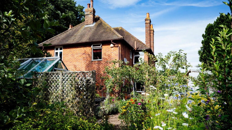 Zweistöckiges Backsteinhaus mit reich blühendem Garten