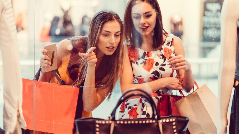 Zwei junge Frauen betrachten eine Handtasche im Schaufenster