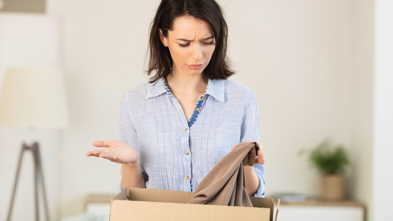 Junge Frau betrachtet mit kritischem Blick ein Kleidungsstück, das sie aus einem Paket ausgepackt hat