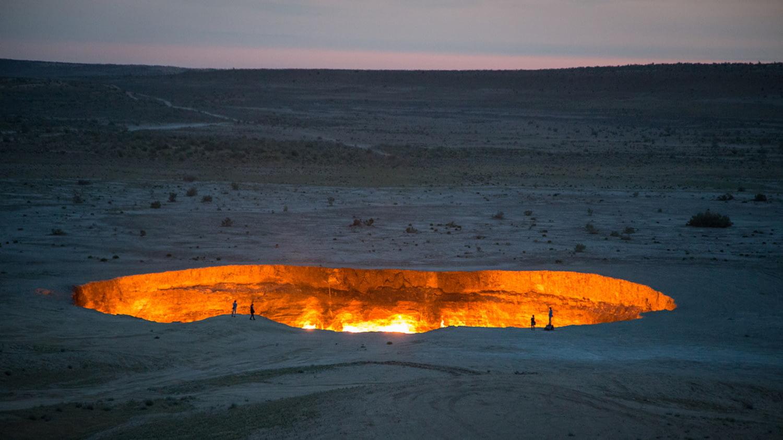 Großes Loch im Wüstenboden, in dem heller Feuerschein zu sehen ist