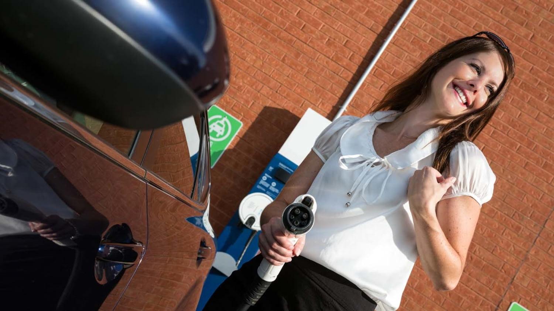 Junge Frau lädt ihr Elektroauto