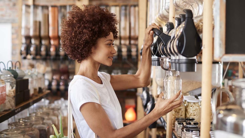 Eine Frau füllt Haferflocken ab in einem Unverpackt-Laden
