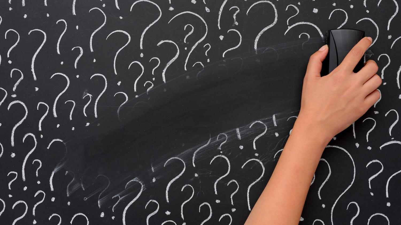 Jemand wischt mit einem Schwamm Fragezeichen auf einer Tafel weg