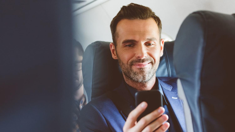 Ein Mann sitzt im Flugzeug und blickt gut gelaunt auf den Bildschirm seines Smartphones