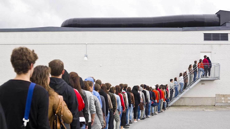 Personen stehen in einer langen Warteschlange vor einer Tür