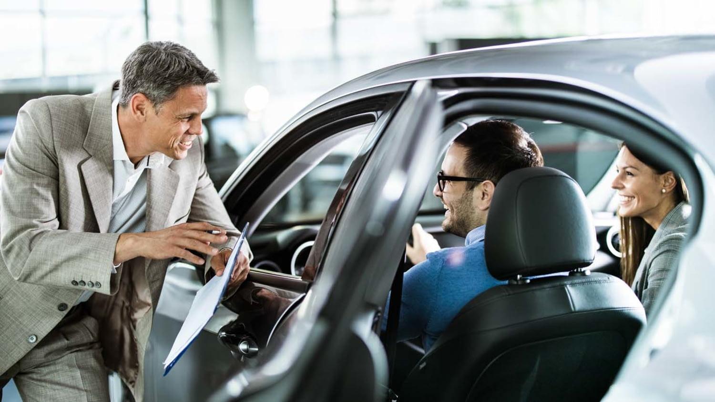 Autoverkäufer im Gespräch mit jungem Paar im Neuwagen