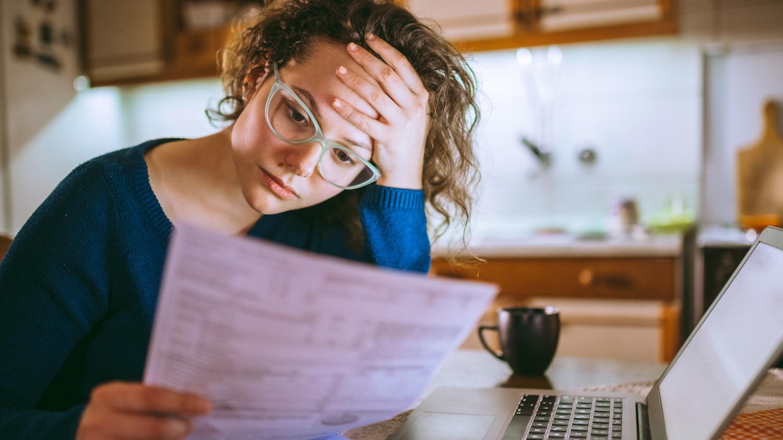 Junge Frau sitzt an einem Tisch vor ihrem Laptop und blickt besorgt auf ein ausgedrucktes Dokument