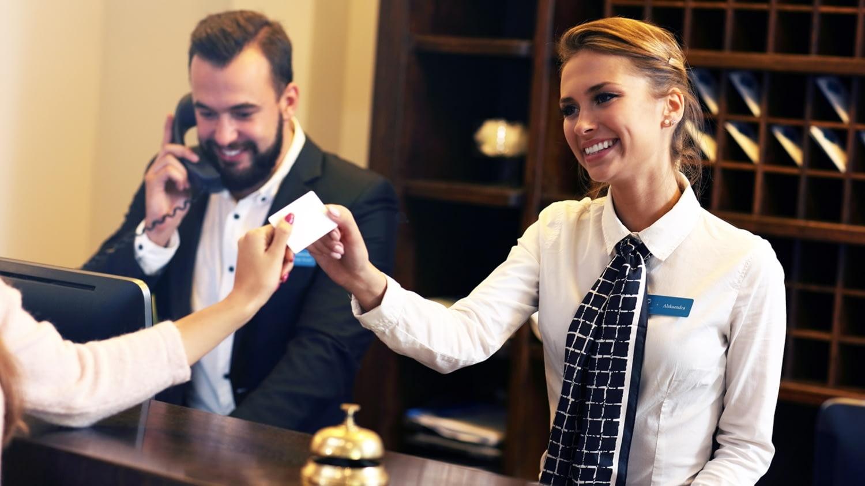 Rezeptionistin in einem Hotel reicht einem weiblichen Gast die Kreditkarte zurück