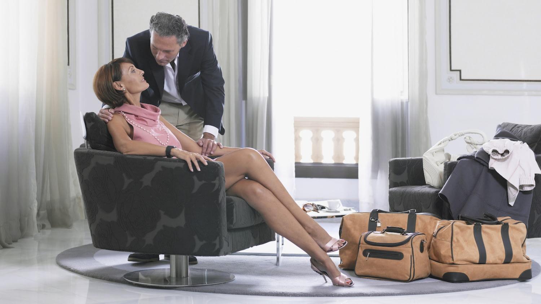 Ein gut gekleideter Mann lehnt sich herunter zu seiner Frau, die neben ihrem Reisegepäck in einem teuren Hotelzimmer sitzt