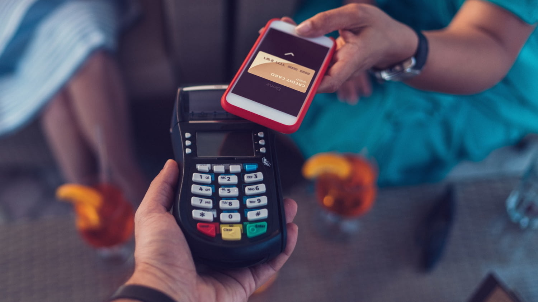 Eine Frau hält ihr Handy zum kontaktlosen Bezahlen mit NFC dicht an das Lesegerät