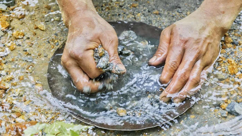 Nahaufnahme zweier Hände, die mithilfe einer Goldwaschpfanne in einem Flussbett nach Gold suchen
