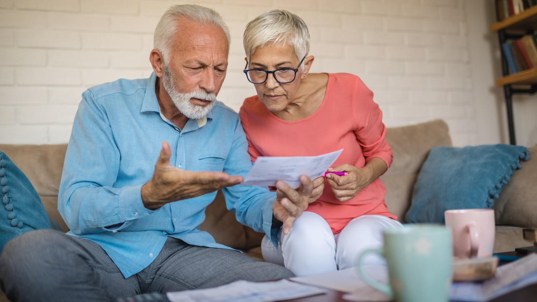 Ein älteres Paar sitzt auf dem Sofa und betrachtet fassungslos ein Schreiben.