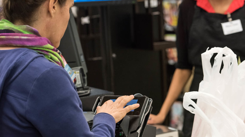 Frau tippt ihre PIN in ein Bezahlterminal im Supermarkt