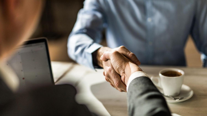 Finanzberater begrüßt einen Kunden mit Handschlag und frisch gebrühtem Kaffee.