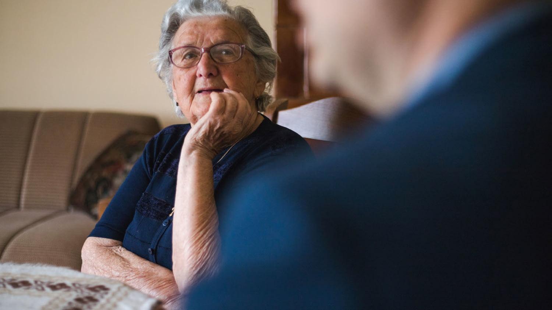 Eine ältere Dame sitzt mit einem Mann am Wohnzimmertisch und hört interessiert zu