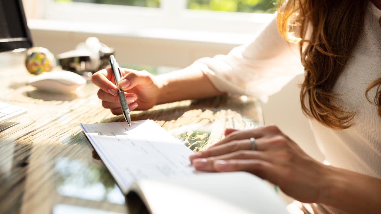 Eine Frau sitzt am Schreibtisch und füllt einen Scheck aus