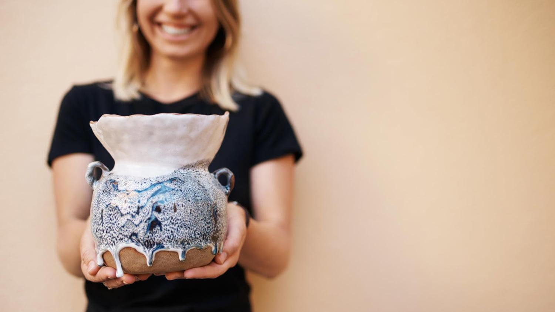 Frau präsentiert eine handgefertigte Tonvase