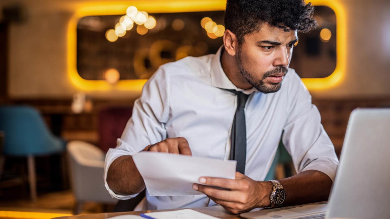 Mann vergleicht Angaben von einem Dokument auf einem Computer