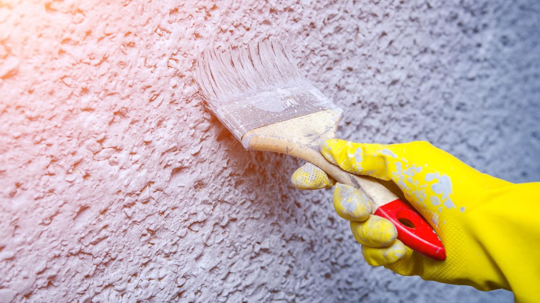 Großaufnahme Pinsel beim Streichen über eine Wand