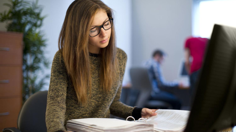 Junge Studentin bearbeitet an einem Büroarbeitsplatz Akten