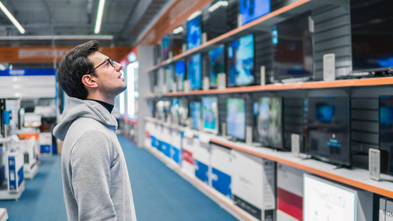 Ein junger Mann sieht sich in einem Elektrofachgeschäft das Angebot an Fernsehern an