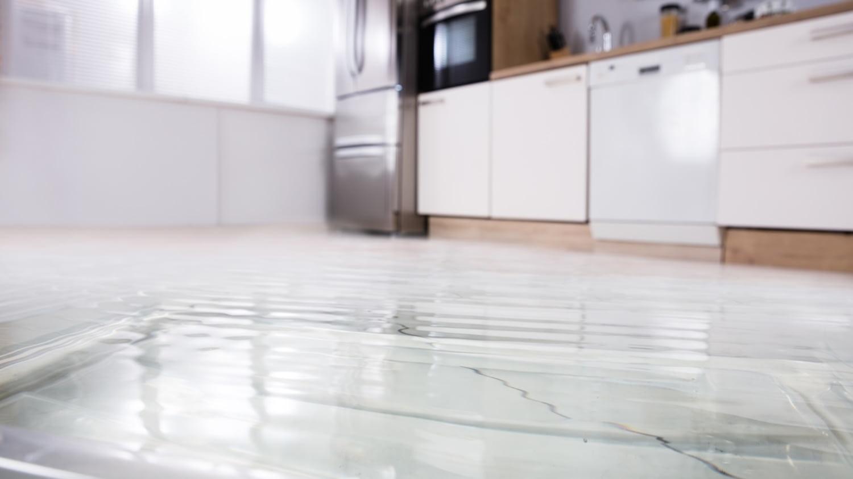 Der Boden einer Küche ist mit Wasser überschwemmt.