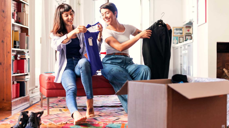Zwei junge Frauen probieren zu Hause Kleidung aus einem Karton an