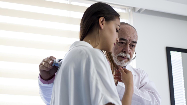 Ein Arzt horcht die Lunge einer jungen Patientin ab.