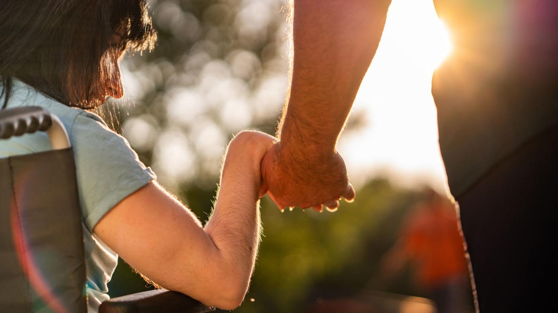 Ein Mädchen im Rollstuhl umfasst die Hand eines Erwachsenen