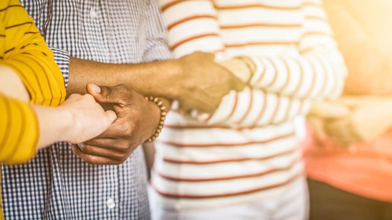 Menschen unterschiedlicher Hautfarbe geben sich die Hände
