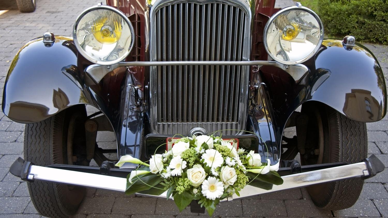 Ein für eine Hochzeit festlich mit Blumen dekorierter Oldtimer.