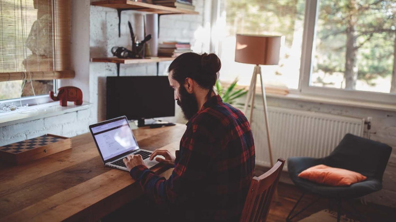 Ein Mann in kariertem Hemd sitzt zu Hause und tippt auf seinem Laptop