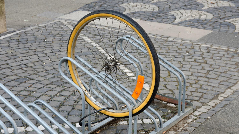 Diebstahlversicherung: An einem Fahrradständer ist nur noch ein einzelner Reifen angekettet