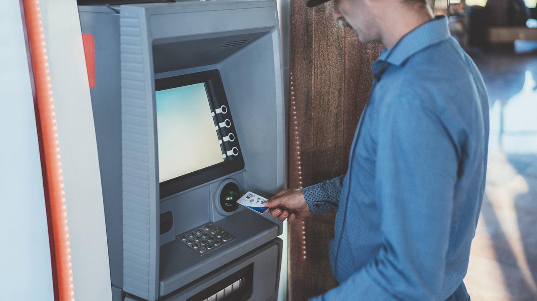Mann führt eine Karte in einen Bankautomaten ein