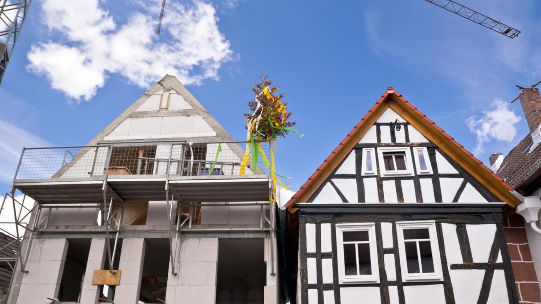 Richtfest bei einem Neubau neben einem renovierten Fachwerkhaus