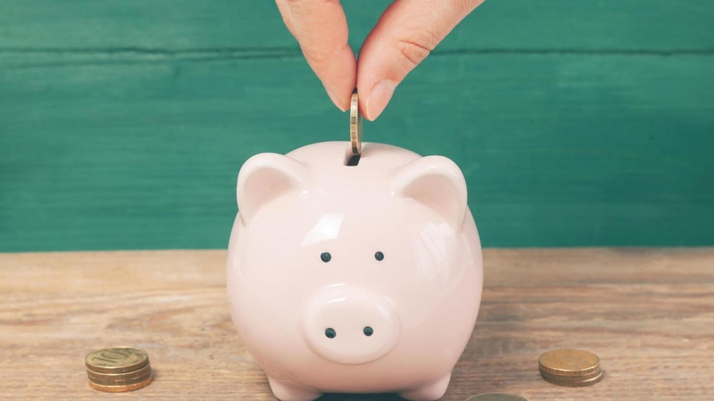 Hand wirft eine Münze in ein Sparschwein