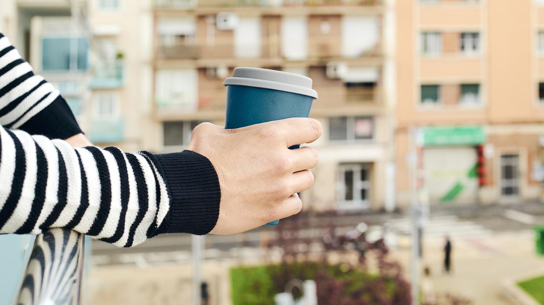 Junger Mann bei einem Kaffee auf dem Balkon