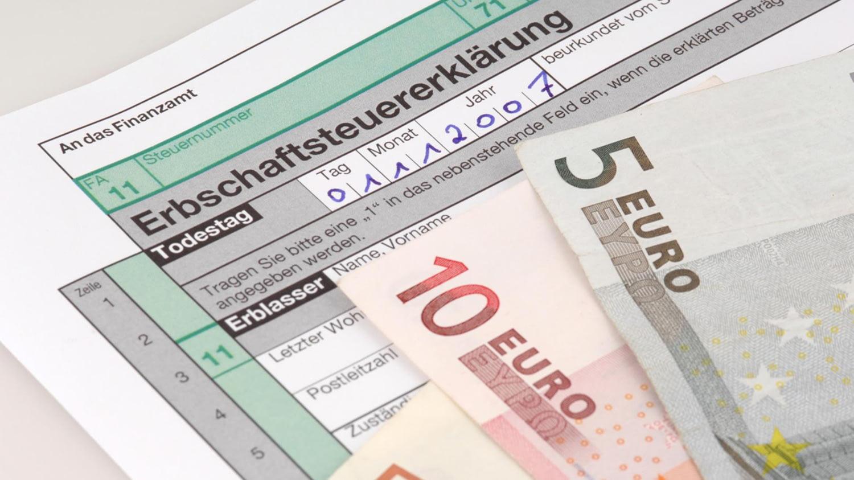 Euro-Scheine auf einem Formular für die Erbschaftssteuererklärung
