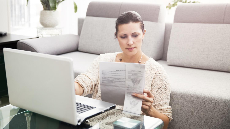 Frau sitzt am Couchtisch vor ihrem Sofa und tippt Informationen von einem Formular in ihren Laptop