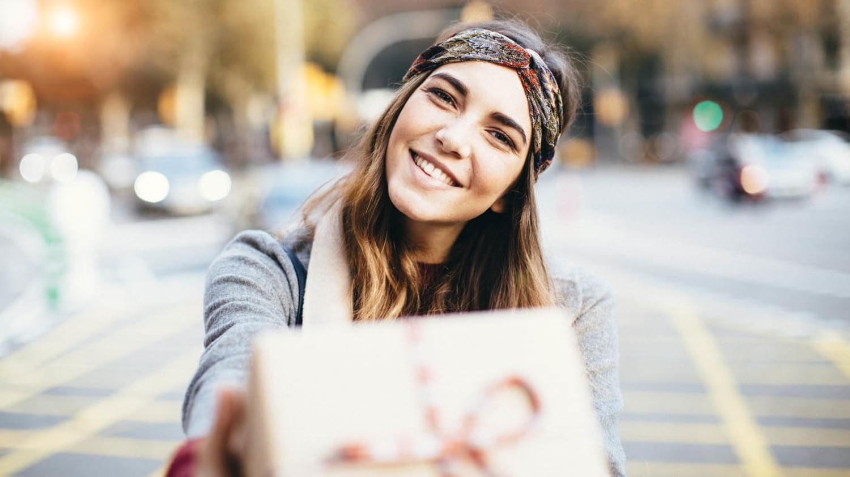 Eine junge Frau ist in der Stadt unterwegs und hält ein Geschenk in die Kamera