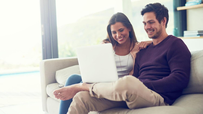 Ein glückliches Pärchen sitzt gemütlich mit dem Laptop auf dem Sofa
