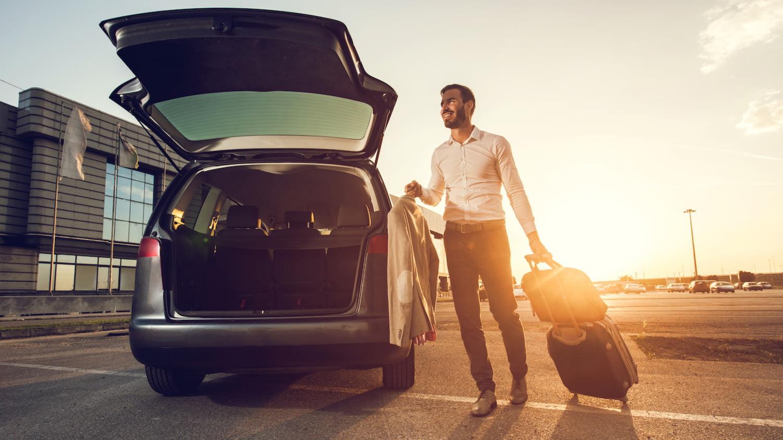 Ein junger Mann will Reisegepäck in die offene Heckklappe eines Wagens einladen