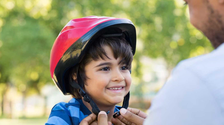 Ein Vater schnallt seinem Kind einen Fahrradhelm um