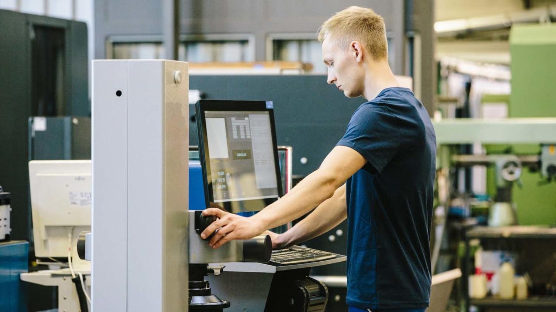 Ein junger Mann steht in einem Betrieb und steuert seine Arbeit an einer CNC-Maschine