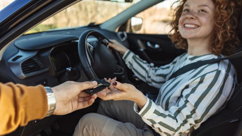 Junge Frau nimmt strahlend den Schlüssel zu ihrem neuen Auto entgegen