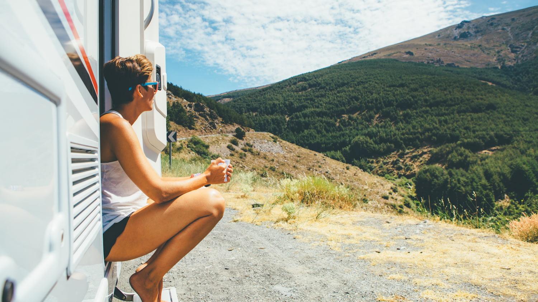 Junge Frau sitzt mit einer Tasse in der Hand auf der Türschwelle eines Wohnmobils und bewundert die Berglandschaft