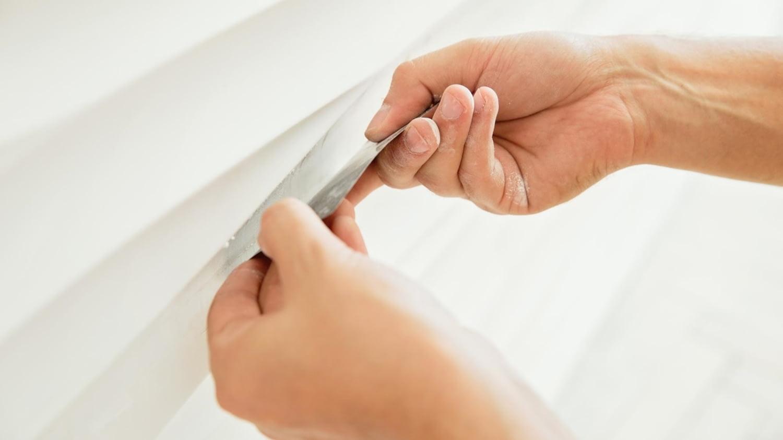 Zwei Hände spachteln mit einer Kreditkarte den Putz einer Wand