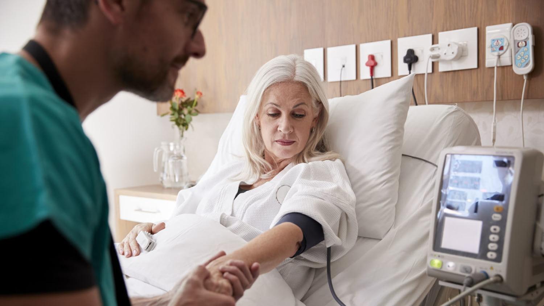 Ein Krankenpfleger misst den Blutdruck einer reiferen Patientin im Krankenhausbett