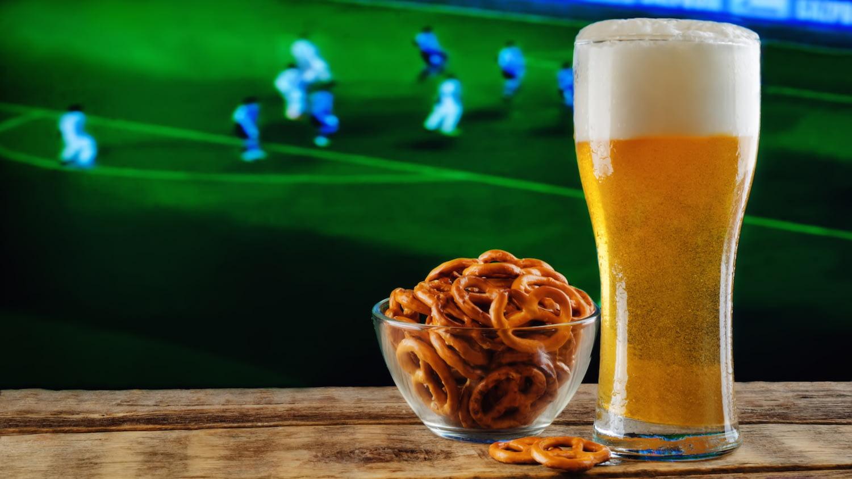 Chips, Mini-Brezeln und ein Glas Bier auf einem Tisch, im Hintergrund läuft Fußball auf einem TV-Bildschirm